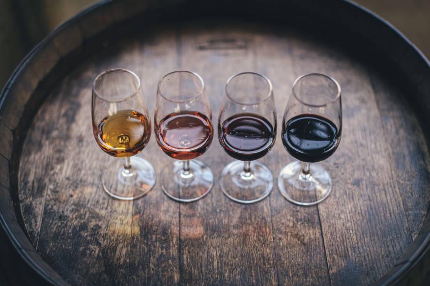four glasses of wine on wine barrel